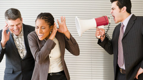 Businessman shouting through bullhorn at co-workers